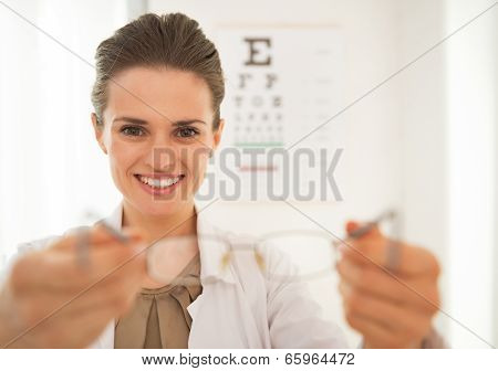 Smiling Ophthalmologist Doctor Woman Giving Eyeglasses In Front