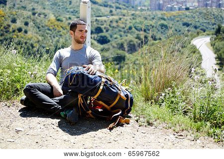 Tourist resting on a halt on a mountain trail and looking away