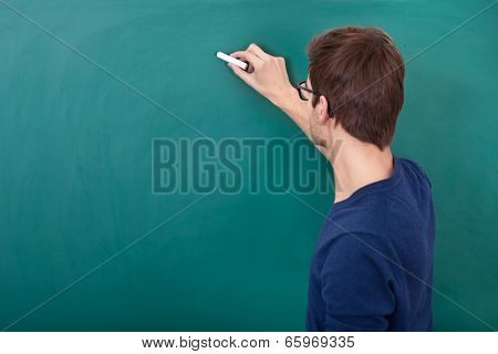 Male Student Writing On Chalkboard