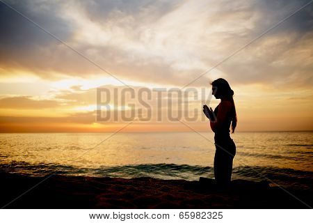 Beauteous silhouette of a slender woman doing yoga on the sea with sunrise