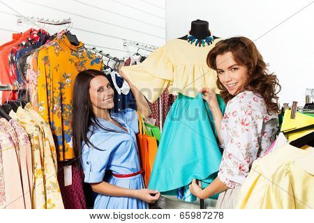 Two Happy Women Holding Blue Skirt In The Shop