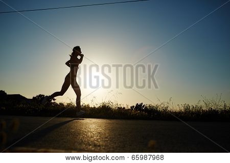 Silhouette of athletic girl running down the beautiful road