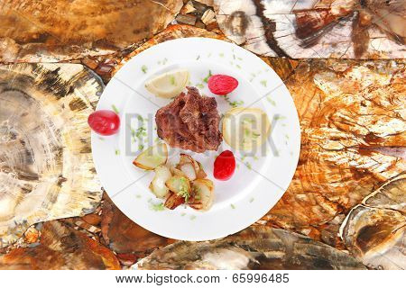 beef bourguignon in wine with artichoke and marinated vegetables on white plate isolated over white background