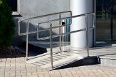 stock photo of wheelchair  - Ramp for wheelchair entry with metal handrails - JPG