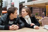 picture of tease  - Young woman teasing man while sitting at outdoor restaurant  - JPG