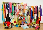 stock photo of messy  - Messy clothes thrown on a shelf - JPG