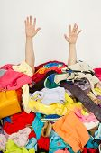 picture of untidiness  - Man buried under an untidy cluttered woman wardrobe - JPG