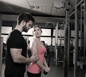 foto of pulley  - cable pulley system personal trainer man and woman learning at fitness gym - JPG