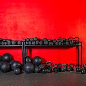 pic of slam  - Kettlebells dumbbells and weighted slam balls weight training equipment at gym red wall - JPG