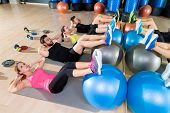 foto of abdominal  - Fitball crunch training group core fitness at gym abdominal workout - JPG