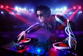 pic of disc jockey  - Handsome disc jockey playing music with light beam effects on stage - JPG