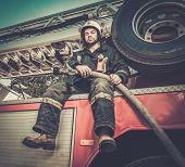 foto of firefighter  - Firefighter sitting on a firefighting truck with water hose  - JPG