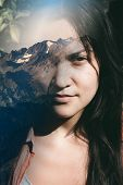 stock photo of superimpose  - Close up of the face of a beautiful young woman dreaming of the countryside looking at the camera with a faraway meditative look with a vision of a scenic landscape superimposed - JPG