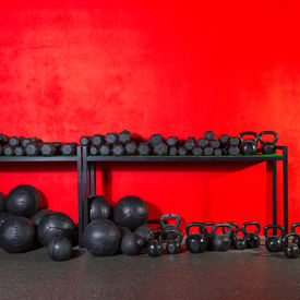 picture of slam  - Kettlebells dumbbells and weighted slam balls weight training equipment at gym red wall - JPG