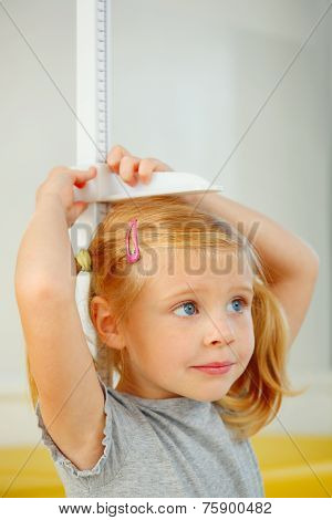 Portrait Of Little Girl Measuring Herself.