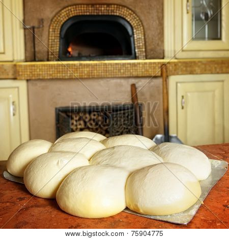 Fresh original Italian raw pizza dough, stone oven in background.
