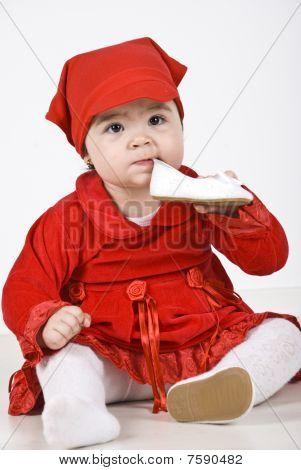 Beautiful Baby Girl Holding A Shoe