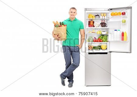 Full length portrait of a young man standing by an open refrigerator and holding a grocery bag isolated on white background