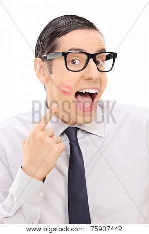 Joyful man showing lipstick kiss mark on his cheek isolated on white background
