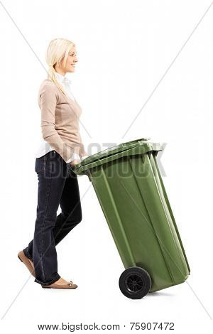Cheerful young woman pushing a garbage can isolated on white background