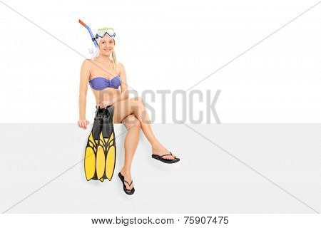 Woman in bikini holding flippers seated on a panel isolated on white background