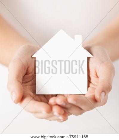 real estate and family home concept - closeup picture of female hands holding white blank paper house