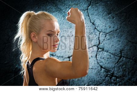 fitness, sport and people concept - sporty woman flexing and showing biceps form back