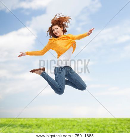 happiness, freedom, movement and people concept - smiling young woman jumping high in air over green background over blue sky and grass background