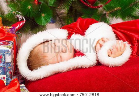 Baby in Santa costume sleeping at the Christmas tree