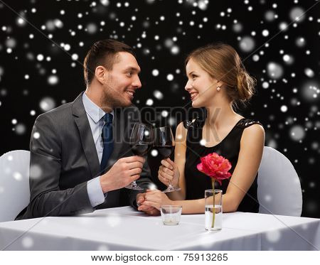 celebration, christmas, holidays and people concept - smiling couple clinking glasses of red wine at restaurant over black snowy background