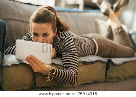 Young Woman Laying On Couch And Using Tablet Pc