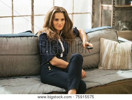Young Woman Watching Tv In Loft Apartment