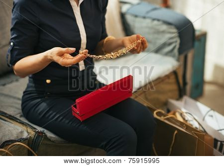 Closeup On Young Woman With Shopping Bags Unpacking Jewelry