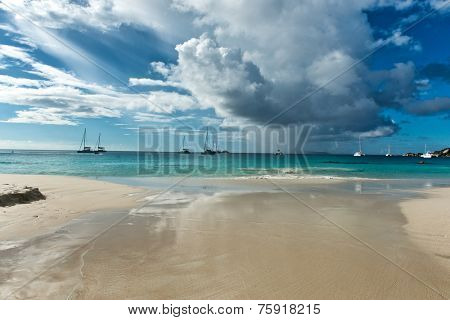 Dramatic clouds over Anse Lazio beach, Praslin in the Seychelles heralding an approaching storm squall with moored yachts in the background