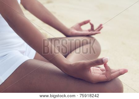 Close up Young Tan Woman Doing Outdoor Root Chakra Pose with Both Fingers on the Knees while Legs are Crossed.