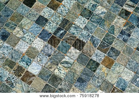 Background pattern and texture of a decorative mosaic with square tiles carved from natural stone or rock