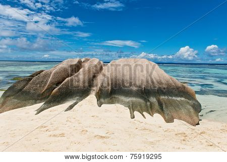 Close up Big Granite Rock on White Beach Sand at Anse Source d'Argent Lagoon in La Digue Island, Seychelles. Captured with Clear Water Lagoon and Light Blue Sky Above.