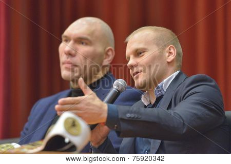 NOVOSIBIRSK, RUSSIA - NOVEMBER 8, 2014: World champion in kickboxing Semen Poskotin and WBA ex-World Champion Nikolay Valuyev talk with children. The meeting dedicated to the Friendship Cup