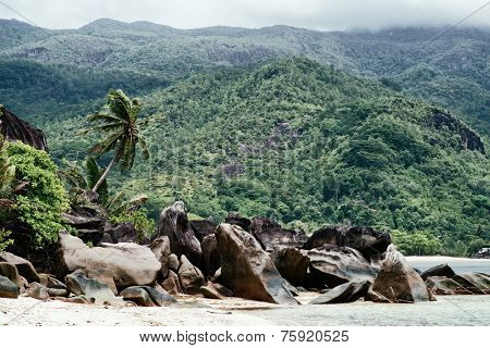 Large Granite Rocks at Beautiful Anse Trusalo at Port Launay in Seychelles. Captured with Huge Green Mountains Afar.