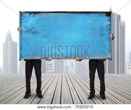 Two Businessman Hold Old Blue Empty Wooden Noticeboard