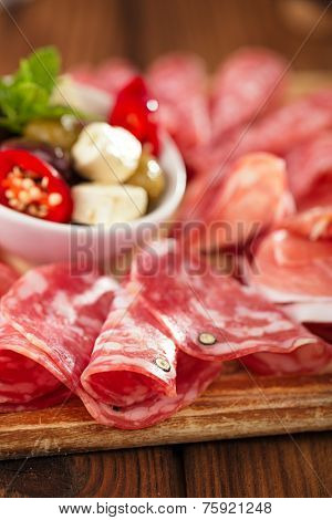 antipasti Platter of Cured Meat,   jamon, olives, sausage, salami,  ciabatta and white wine glasses on textured wooden table