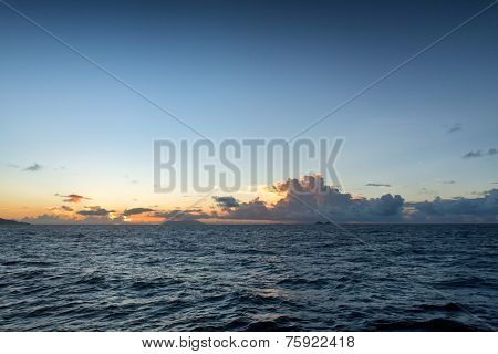 Colorful orange tropical sunset behind cumulonimbus clouds towering above a calm blue ocean