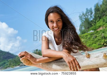 Close up Smiling Pretty Woman Leaning on Dry Tree Branch, with Crossed Arms, While Looking at the Camera. Captured on a Sunny Summer Day.