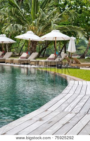 Tranquil pool at a tropical resort with a curving wooden deck leading to vacant recliner chairs and umbrellas for that idyllic summer vacation