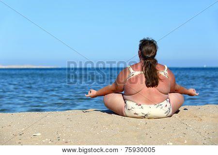 overweightl woman meditation on beach near sea