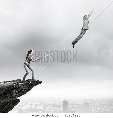 Woman holding on rope businessman trying to escape
