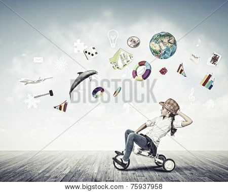 Little cute girl of preschool age riding tricycle. Elements of this image are furnished by NASA