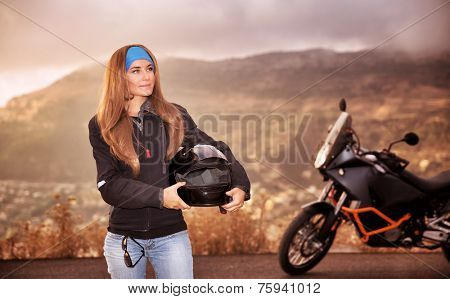 Beautiful biker girl standing on the road with helmet in hands near motorbike, traveling in overcast weather along high mountains, active lifestyle concept