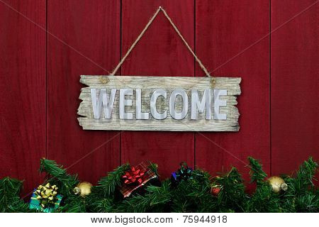 Welcome sign with Christmas garland and presents border hanging on antique red wooden background