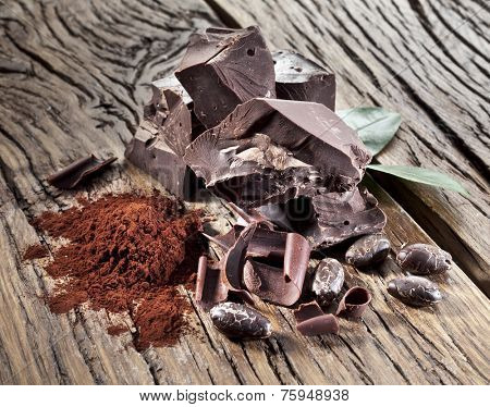 Chocolate and cocoa bean over wooden table.